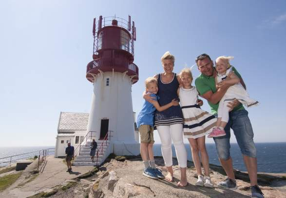 Family smiling in front of Lindesnes lighthouse