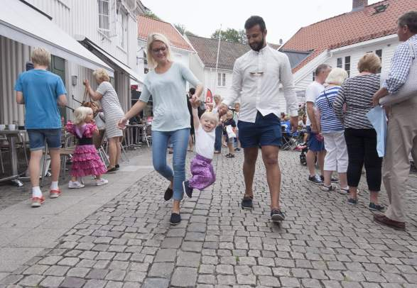 Man and woman walking through a shoppingstreet holding a child between them