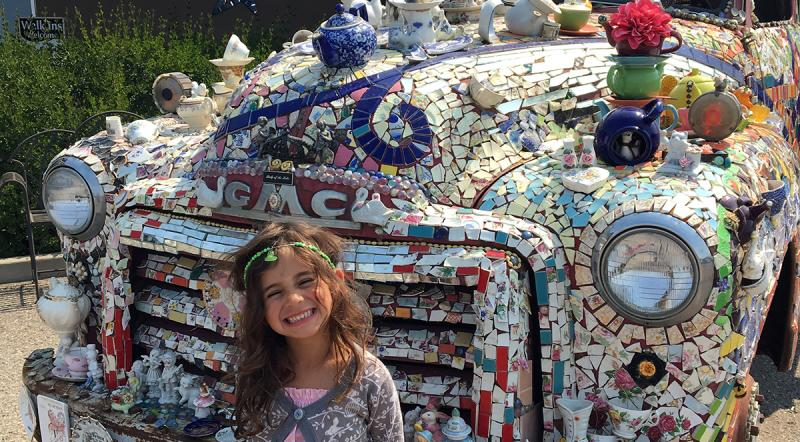 Posing in front of a car decorated in tile and teacups at Lady of the Lake, Brandon, Manitoba