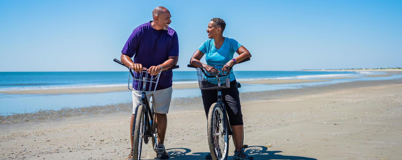 A couple enjoys a bike ride along seven miles of undeveloped beach on Little St. Simons Island, Georgia