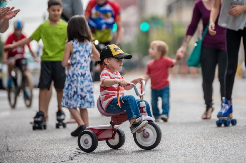 Toddler riding tricycle during Open Streets ICT downtown Wichita festival/event