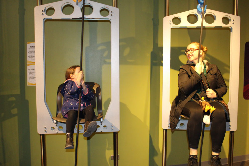 An adult and a child sitting in metal pulley chairs pull ropes to raise the chairs.