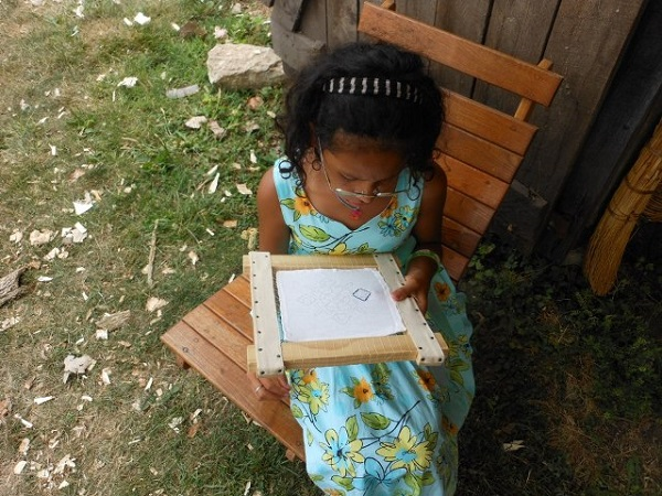 A little girl does some sewing