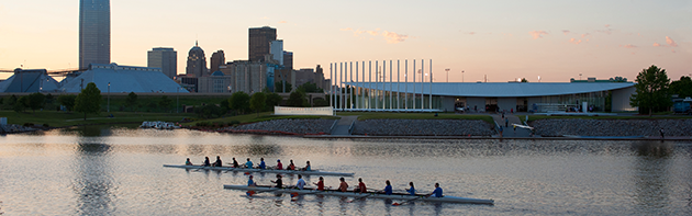 Image of the Oklahoma City Skyline, in the foreground are rowers rowing in the Oklahoma River.