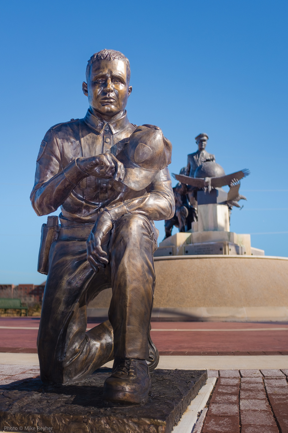A Bronze Sculpture of a Police Offer Kneels at the The 9/11 Flight Crew Memorial in Grapevine