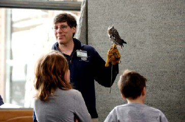 One of The Wild Center's owls, shown here with head curator David Gross, is one example of the Center's new Mother of Invention theme for 2009. Researchers are working to understand the qualities of owl's wings to make quieter and more efficient fan blades.