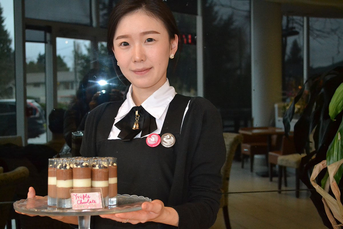 One of Sugarholic's smartly dressed servers shows the Triple Chocolate dessert, one of the many decadent treats offered daily at this Aberdeen Centre eatery.
