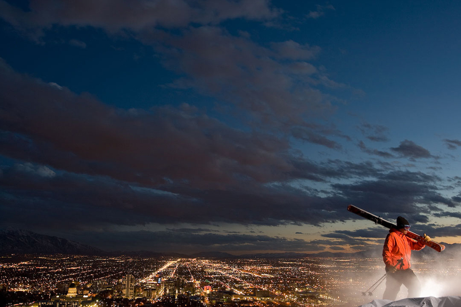 Skier Hiking Above the City at Night