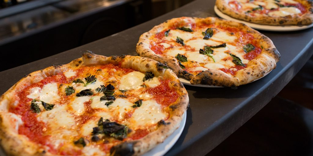 Fresh wood-fired pizza on a gray counter top
