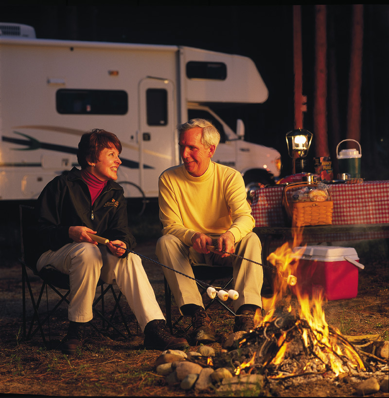 couple roasting marshmallows on a campfire beside their RV