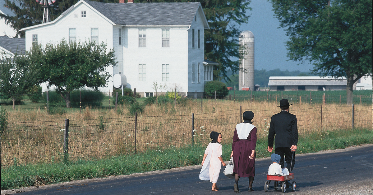 Amish family of four walking together on a road in Elkhart County in front of a white home