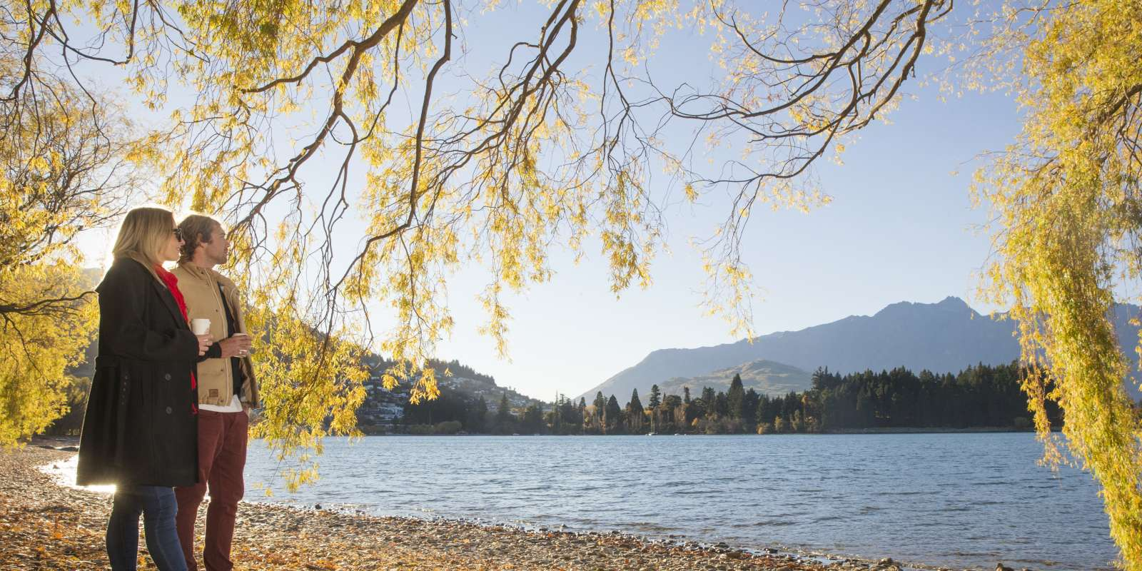 Couple having coffee beside Lake Wakatipu in Autumn