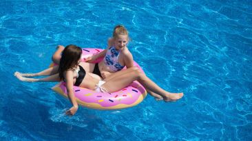 two-girls-sitting-on-pink-doughnut-pool-float-1548774