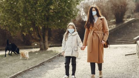 mother-with-daughter-in-face-masks-walking-in-park-4000622