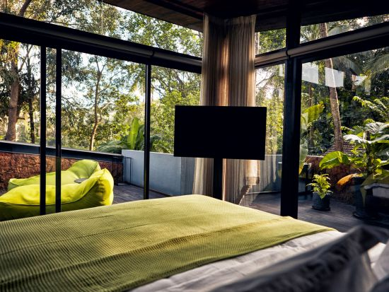 Bedroom with glass windows at one of the best villas in North Goa - Villa in Palms by Vescapes