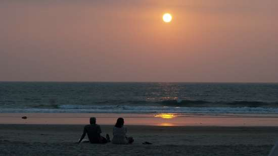 Couple sitting by the beach, Honeymoon Special Volvo Package, Amara Vacanza Grand Inn