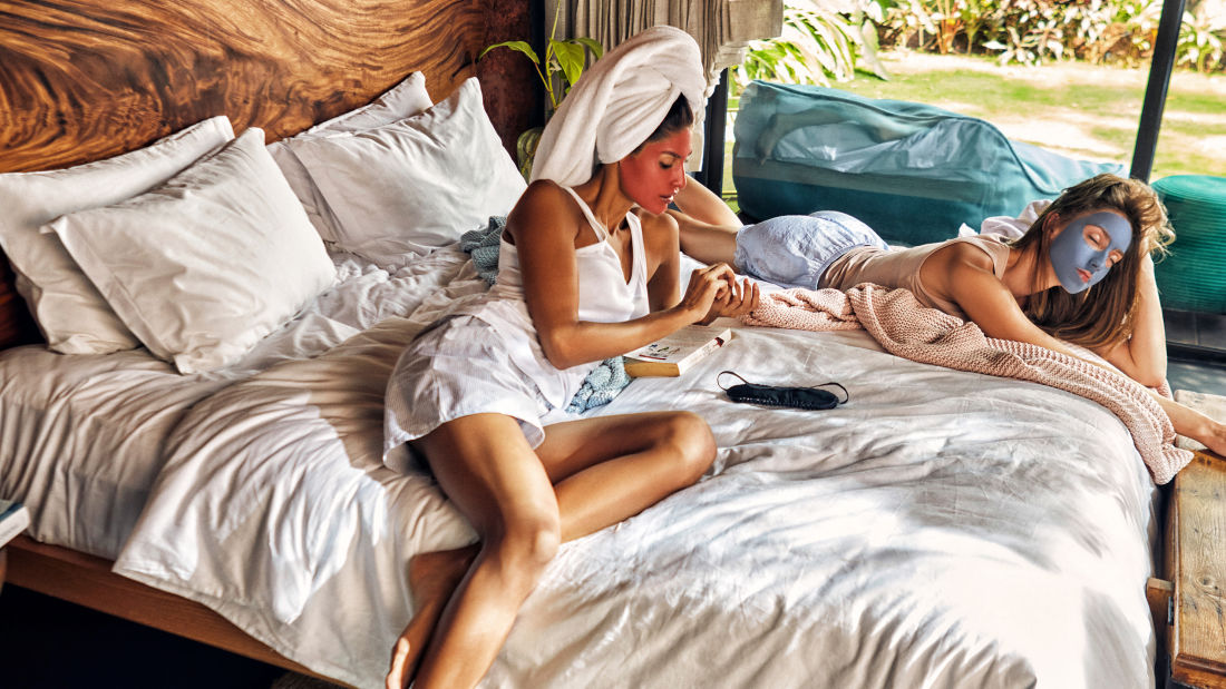 Women with facemasks lounging in the bedroom of the villa for rent in North Goa
