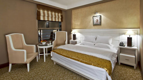 Bed and chairs in the Premium Suite rooms in Patna