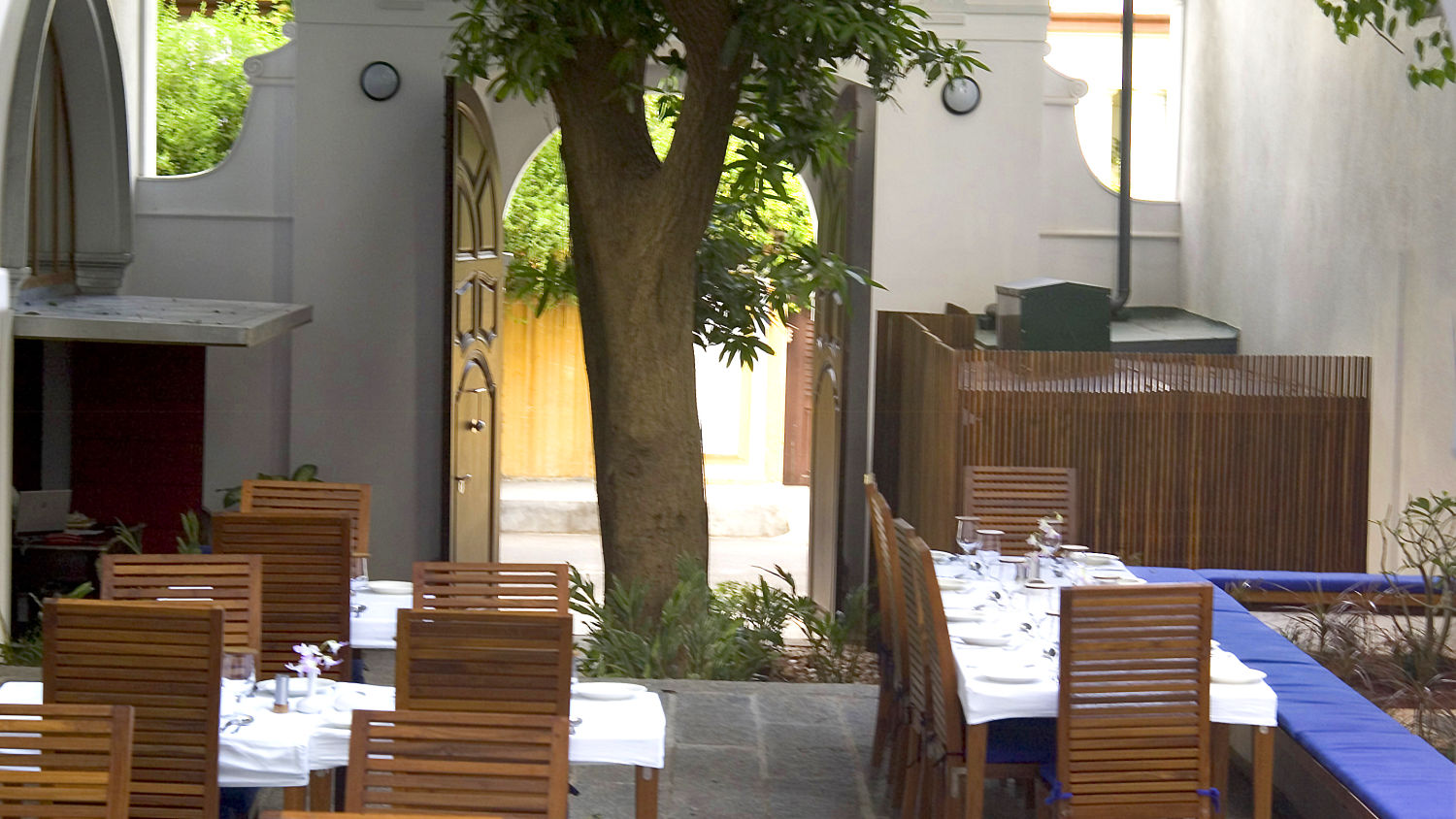 Le Dupleix - The 200 yr old mango tree forms a beatiful canopy in the open air courtyard restaurant a