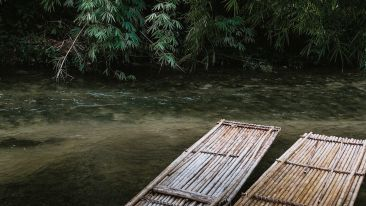 two-long-bamboo-rafts-by-the-side-of-a-shallow-river-3042375