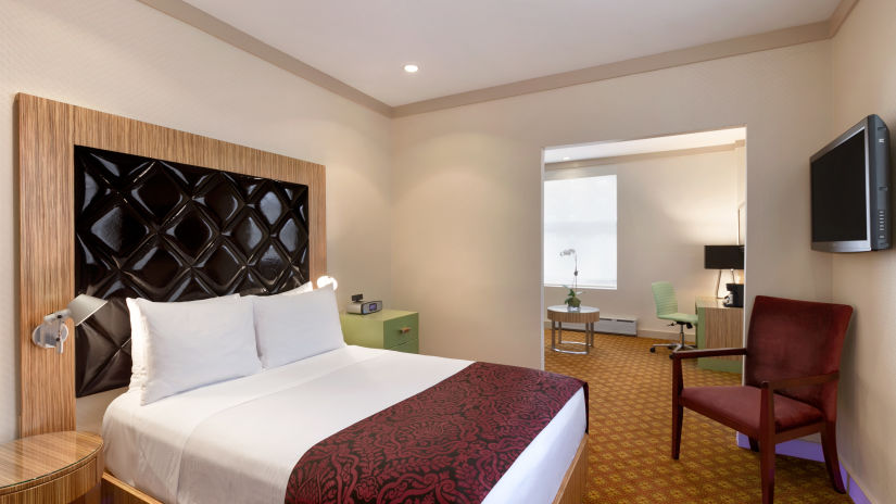 A suite with a comfortable bed, chair and television