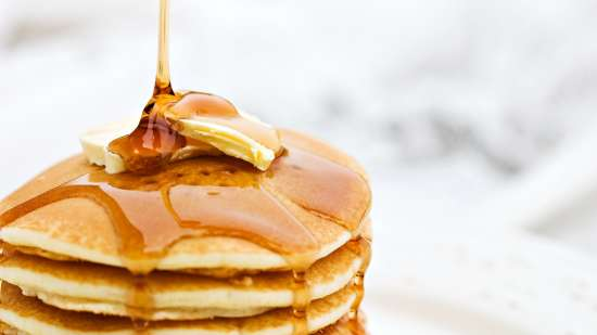 Honey being drizzled onto buttered pancakes