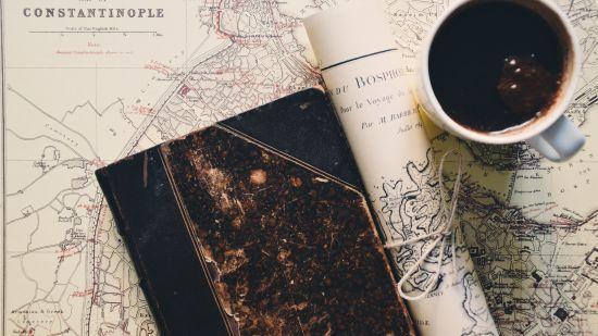 black-coffee-in-mug-near-rolled-paper-and-hardbound-book-2305765