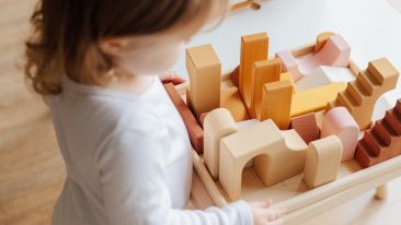 unrecognizable-little-girl-playing-with-wooden-blocks-at-3933033
