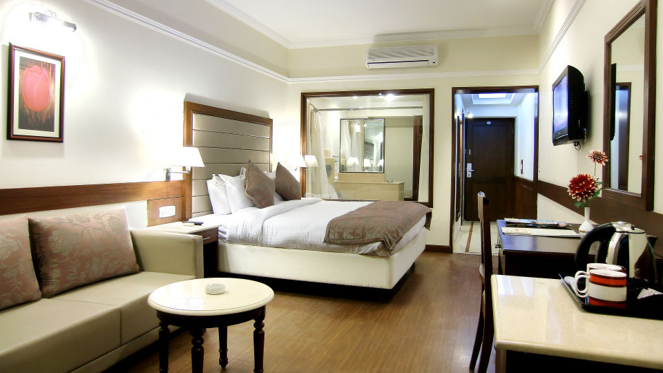 Room with large sofas and a table, Rooms in Mussoorie, Hotel Madhuban Sarovar Portico, Mussoorie