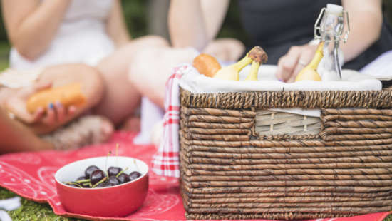 bowl-of-cherry-and-picnic-basket-with-people-in-the-background 23-2147908317