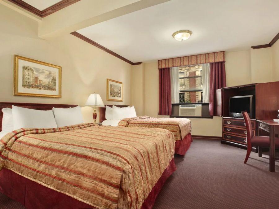Spacious room with two beds, a work desk and modern artwork