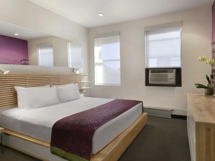 rooms with beds and large windows that overlook the surroundings