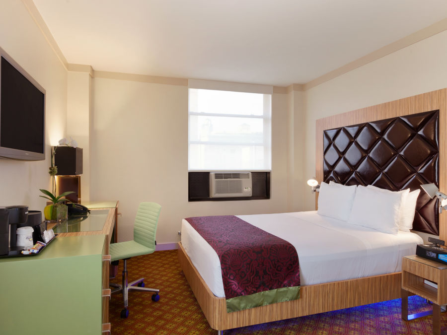 Window side rooms featuring a bed, television and a night stand