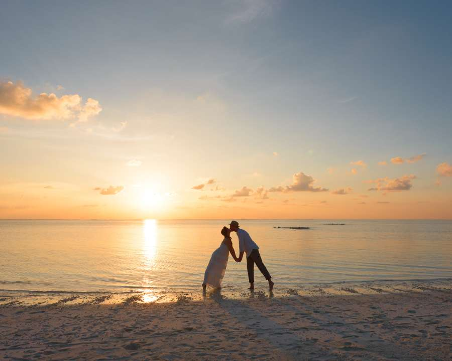 alt-text man-and-woman-standing-on-shore-kissing-1024983