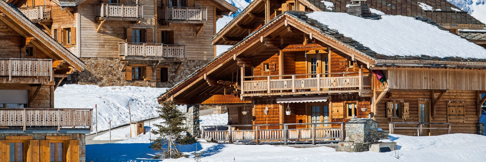 Træfarvet ski chalet i seen med blå himmel i Alpe d Huez