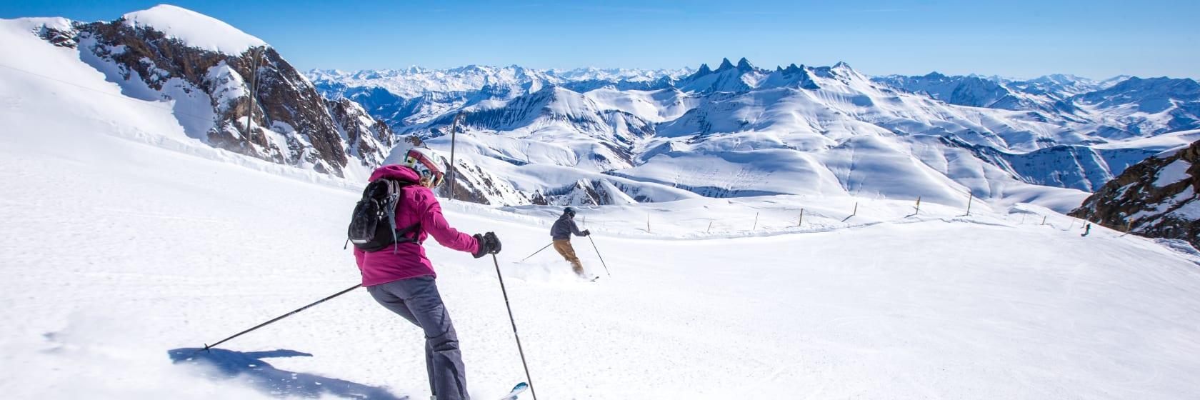 Skiløbere på vej ned ad pisten med blå himmel i Alpe d Huez