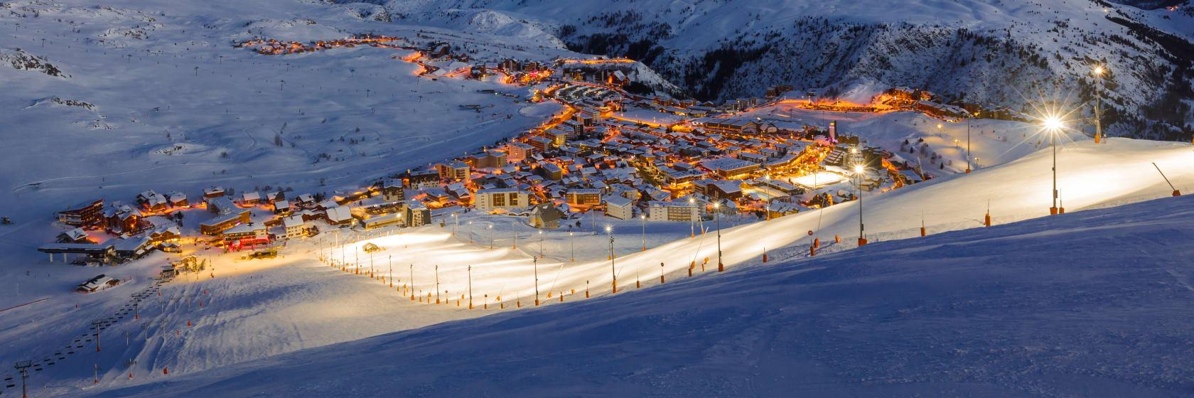 Sne og oplyste pister ved solnedgang i Alpe d Huez