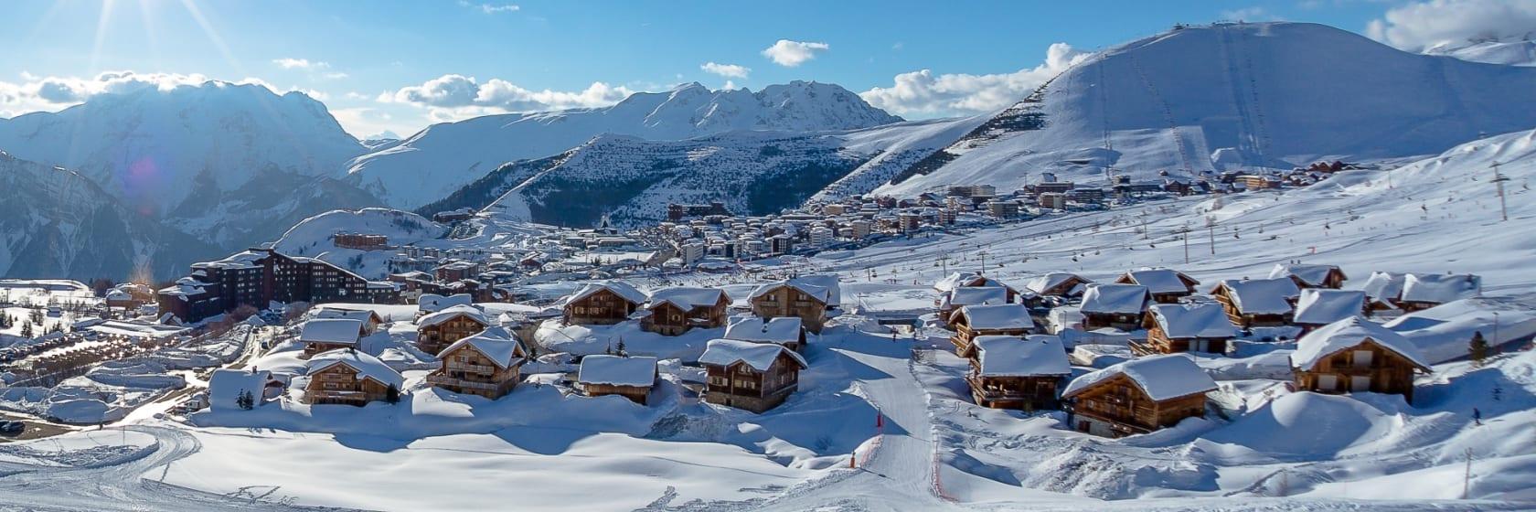 Sneklædte hoteller i skiområde med blå himmel i Alpe d Huez