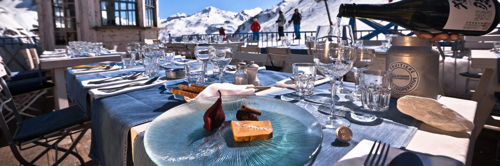 Frokost udendørs i solen på restaurant med mad og vin på skiferie i Val d Isère