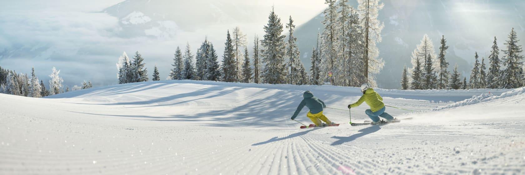 Skiløbere på piste med snebeklædte træer og bjerge i Schladming