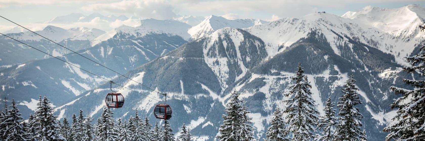 Skilift blandt sneklædte træer og bjerge i Saalbach