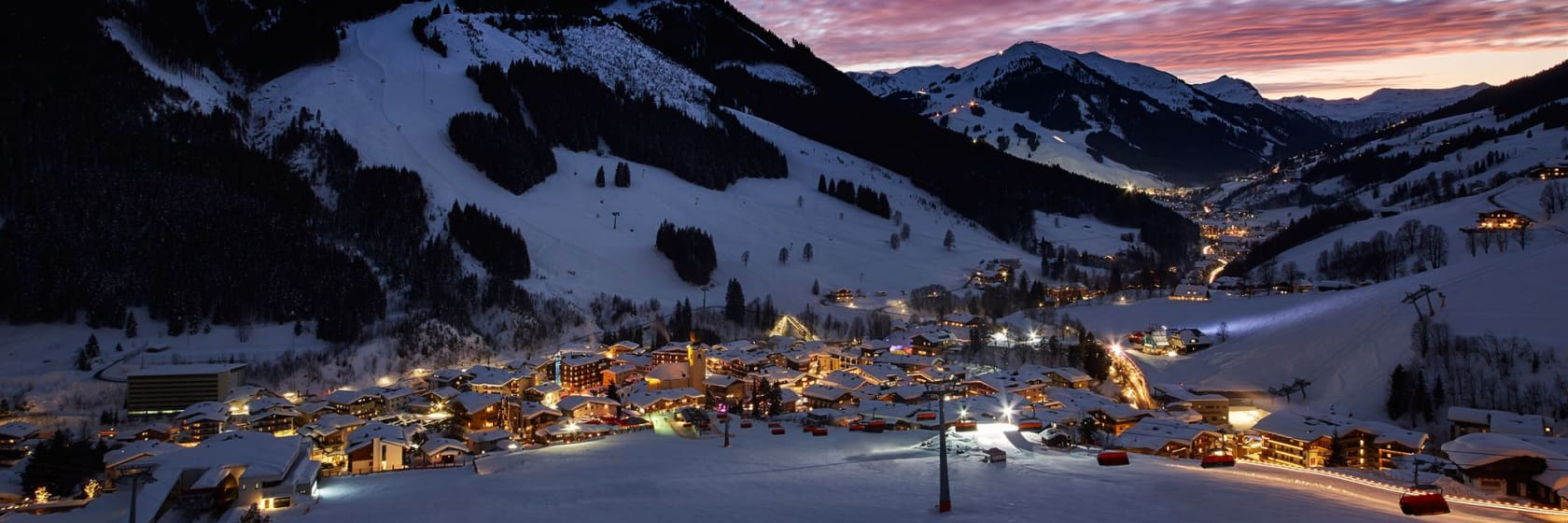 Skisports om natten med lyse i husene i Østrig