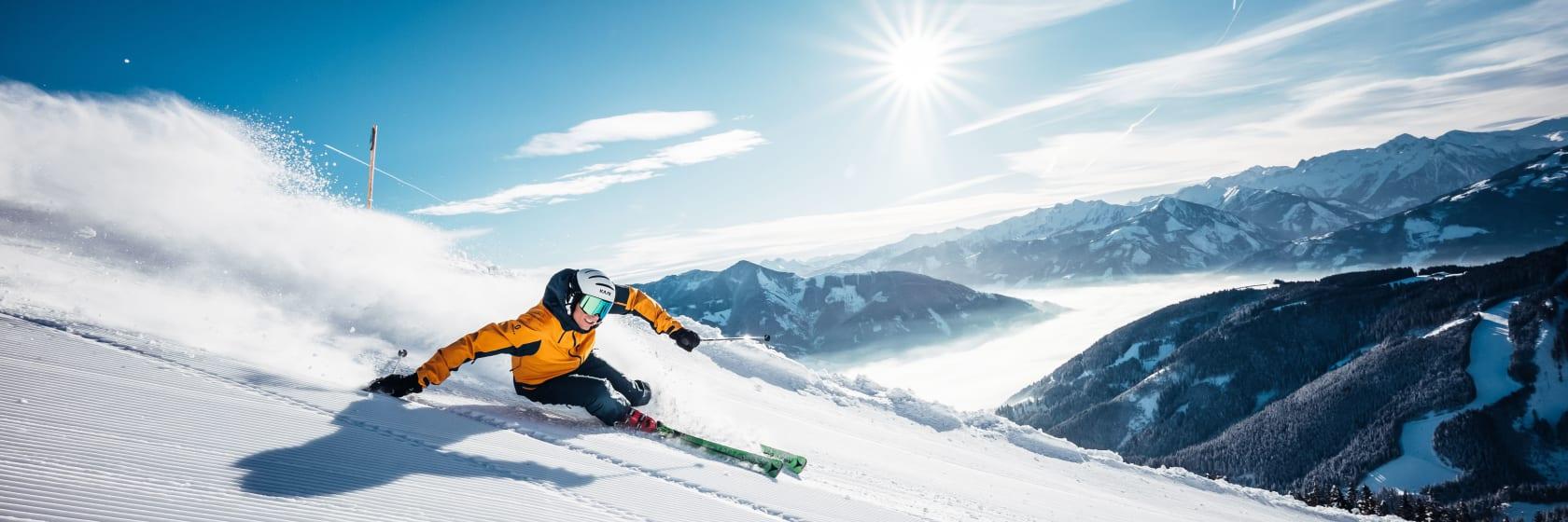 Skiløber i gul jakke i sneen med blå himmel i Zell am See