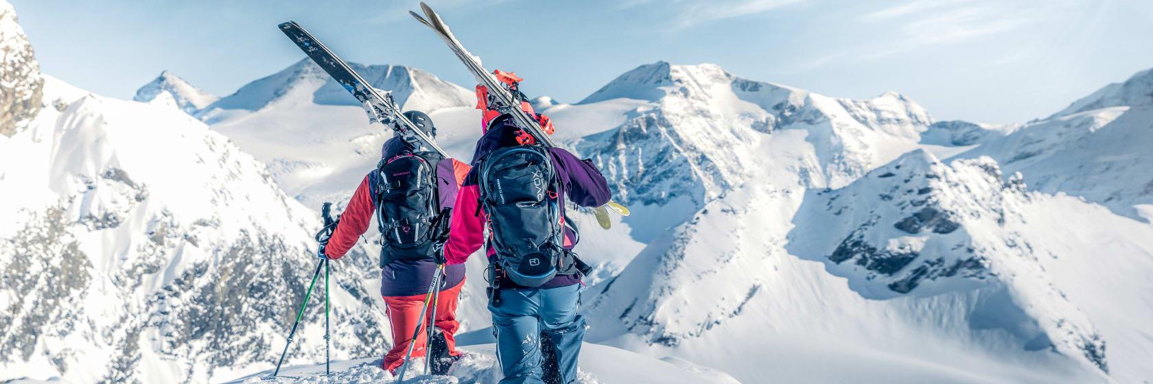 Skiløbere med ski på ryggen gående i dyb sne i bjergene