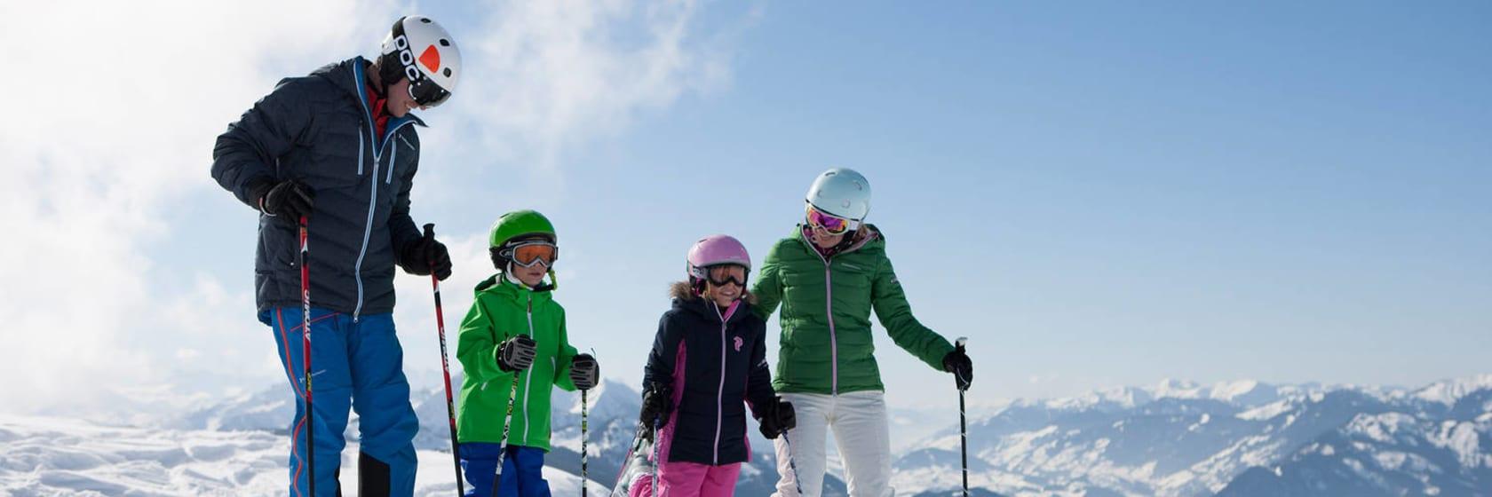 Familie på skiferie i hvid sne og blå himmel