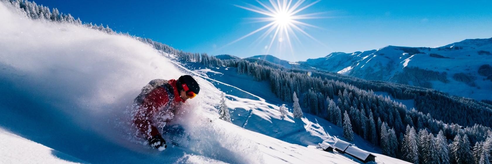 Skiløber på ski i hvid sne med blå himmel i baggrunden