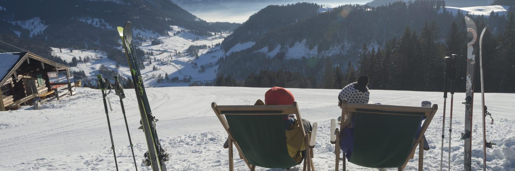 To personer siddende i liggestole med skiene i sneen og udsift over bjergene i solen