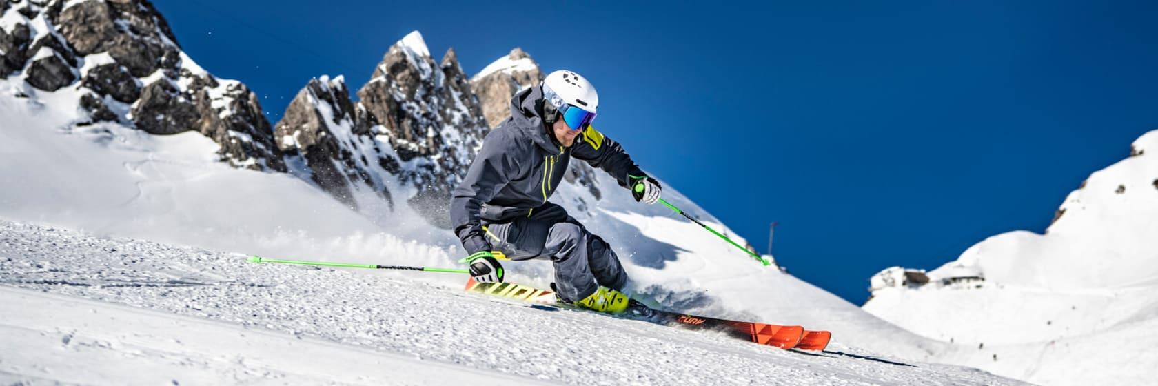 Skiløber på pisten i den hvide sne på skiferie i Alperne