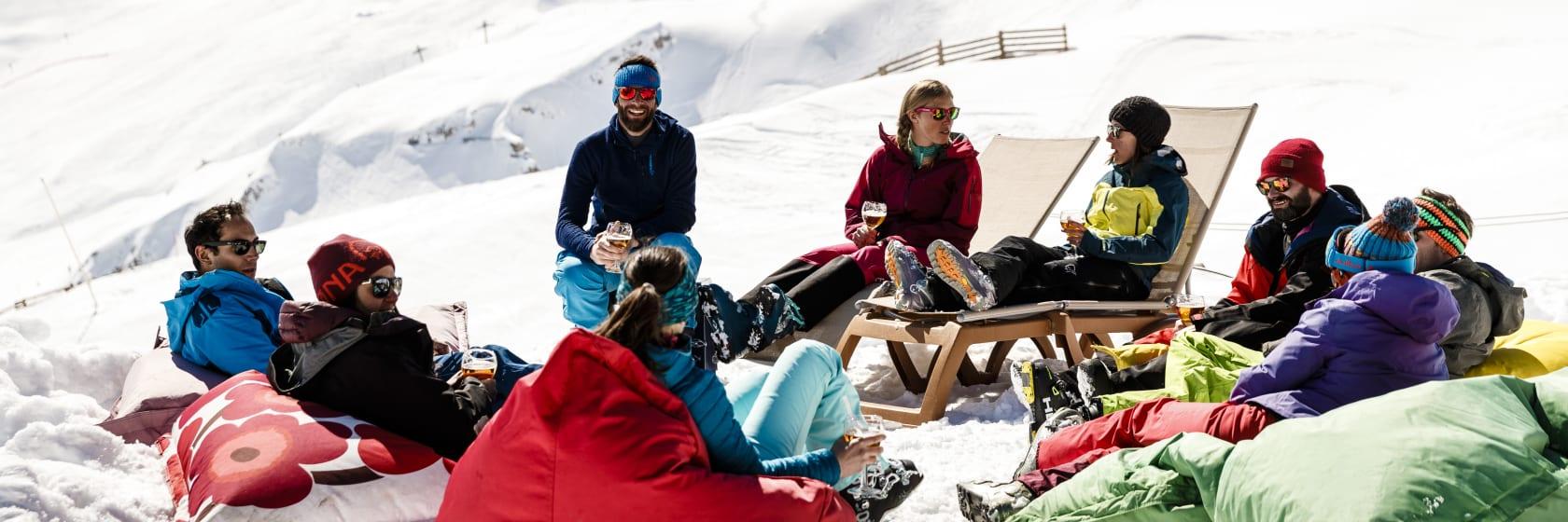 Glade mennesker på skirejse i sneen med udsigt over bjerge