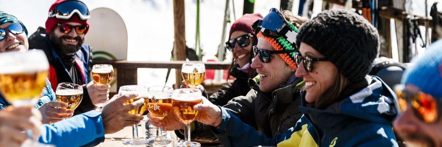 Glade skiløbere drikker øl i solen på skiferien